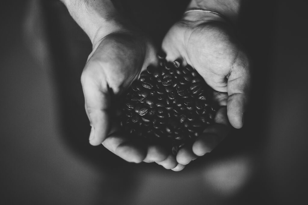 A man holding coffee beans in his hands.