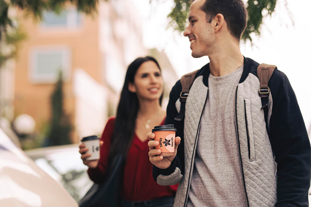 Man and woman enjoying a walk holding their paper cup coffees.