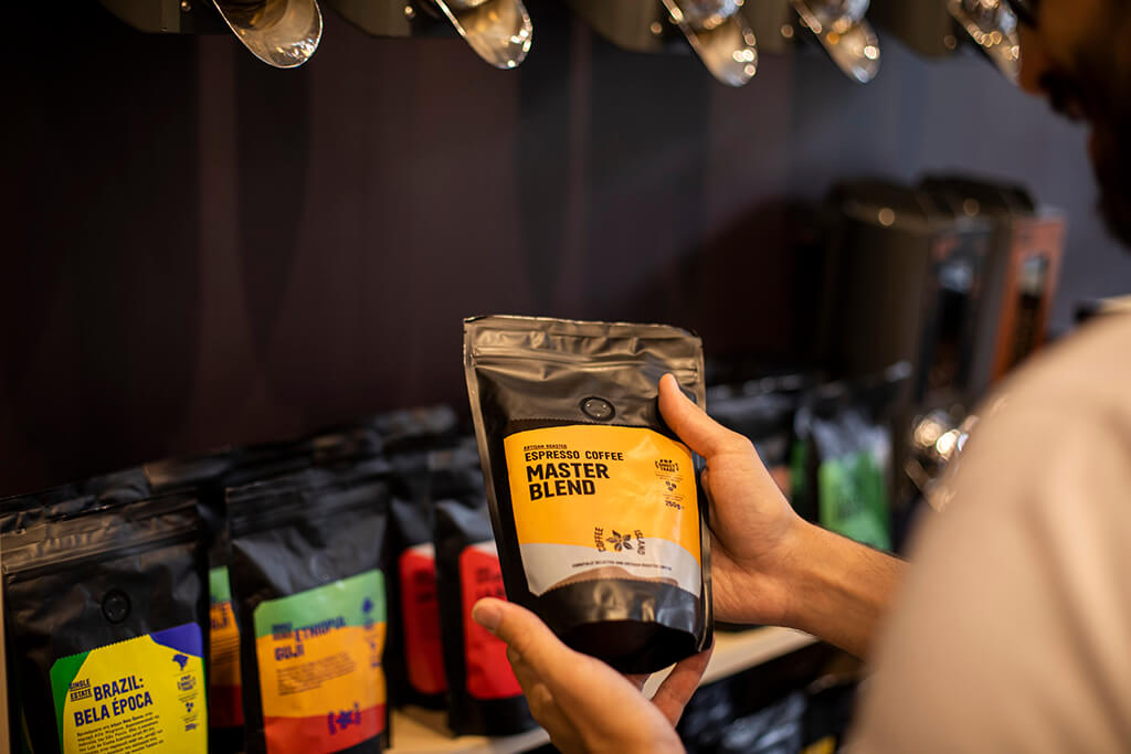 A man holding a master blend coffee packaging inside a Coffee Island store.
