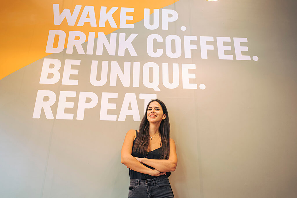 Woman standing below a wall-message inside a coffee island store.
