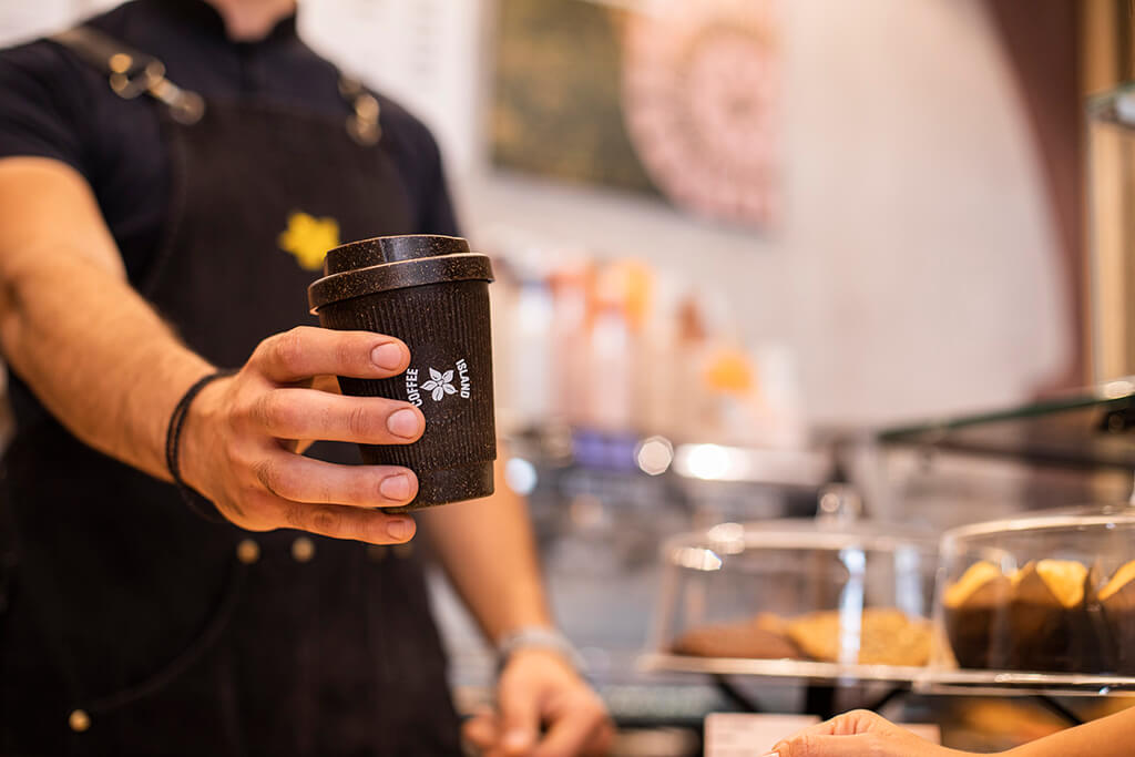 A barristi holding a kaffee form reusable cup