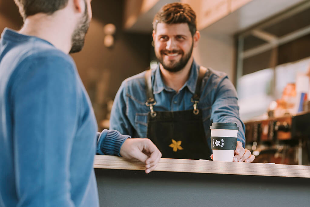 A barristi giving a customer coffee in a reusable cup