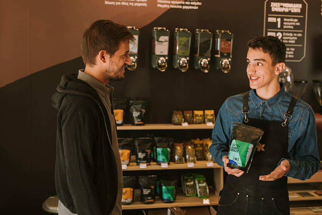 Coffee Island stuff showing a coffee package to a customer.