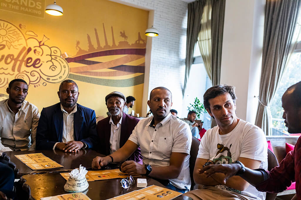 Ethiopian producers and Coffee Island stuff sitting in a coffee place in Ethiopia