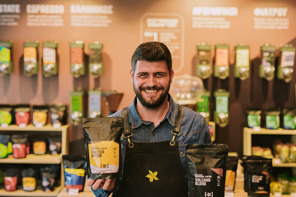 A man holding a master blend and a volcano blend inside a Coffee Island store.