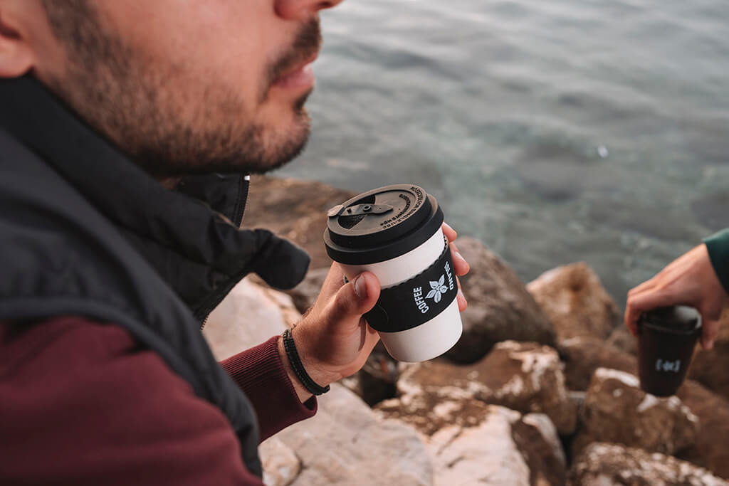 A man drinking tea in a reusable cup from Coffee Island