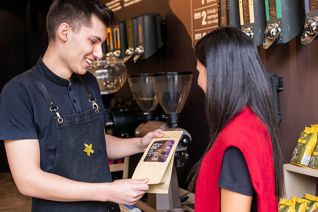 A man giving a coffee package at a woman in a Coffee Island store.