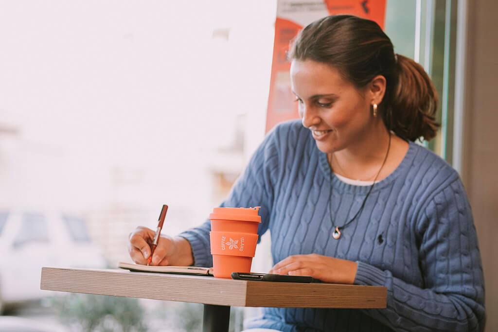 A woman writing in her notepad while enjoying her tea in a reusable cup from Coffee Island