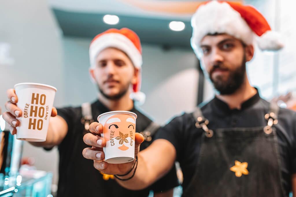 Two baristi men holding Coffee Island Christmas cups