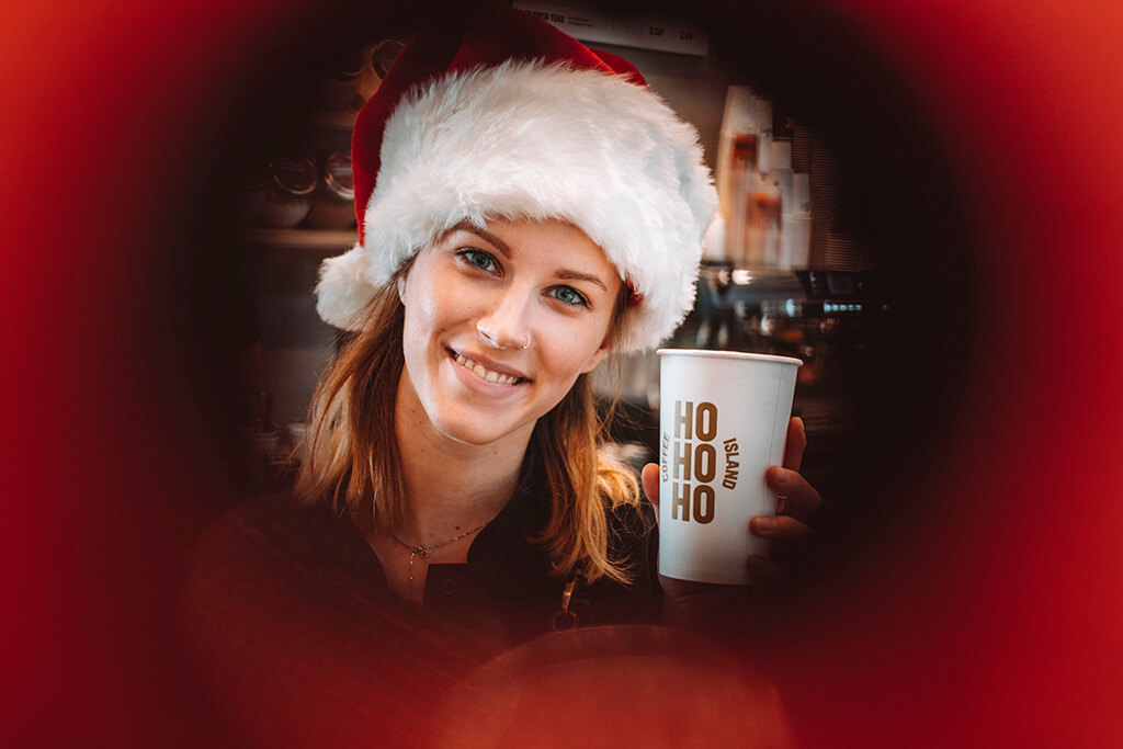 Baristi woman with Christmas spirit holding a Coffee Island Christmas cup