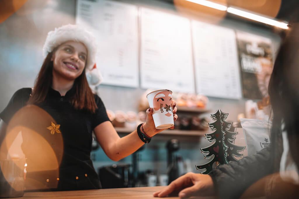 Baristi woman offering coffee in a Coffee Island Christmas cup