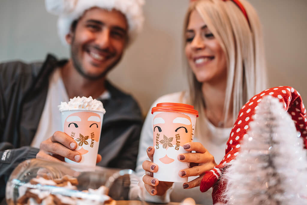 A man and a woman happily enjoying their Coffee Island Christmas beverages