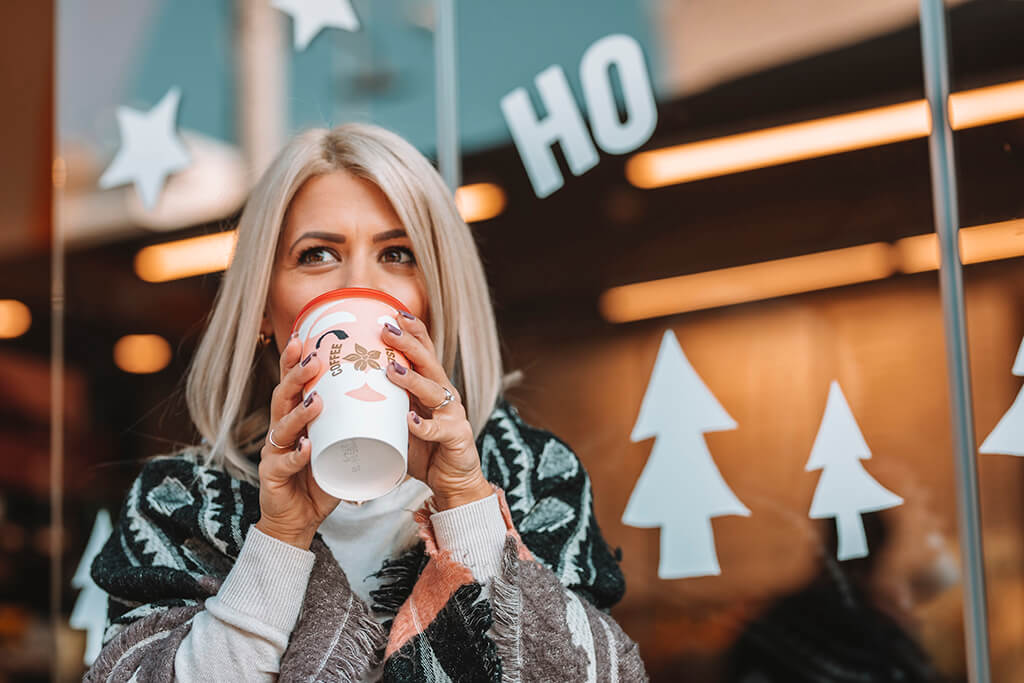 Woman drinking coffee in a Coffee Island Christmas cup