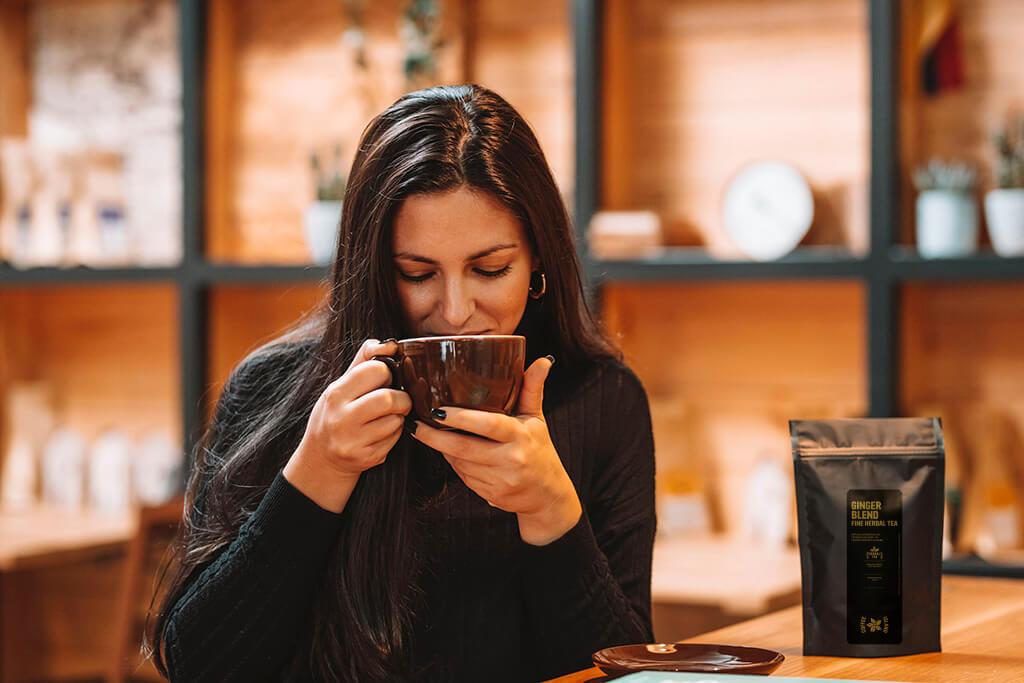 Woman drinking Coffee Island's Ginger Blend Tea