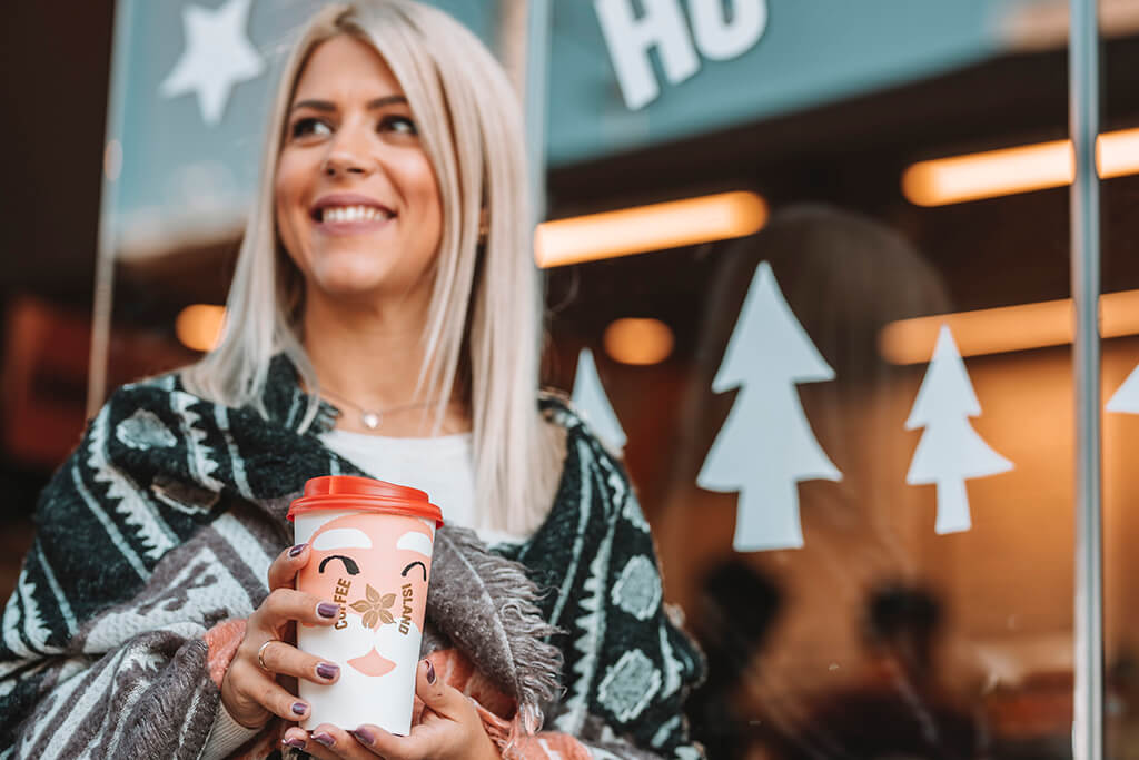 Woman happily holding Coffee Island's Christmas Santa Claus cup