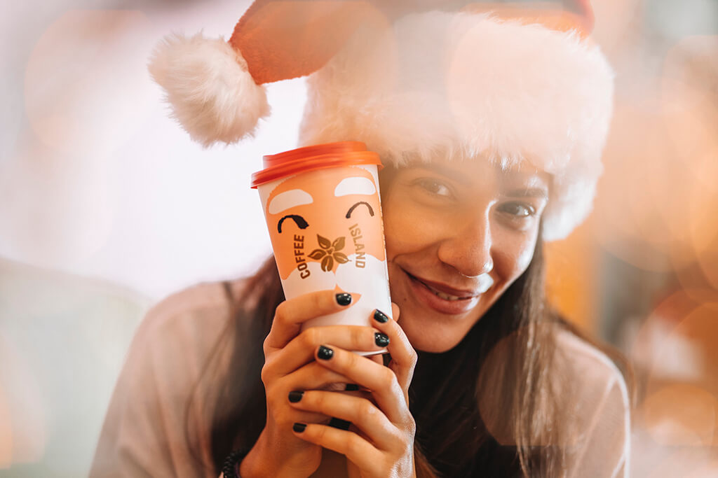 Happy woman holding her Coffee Island Santa Christmas cup