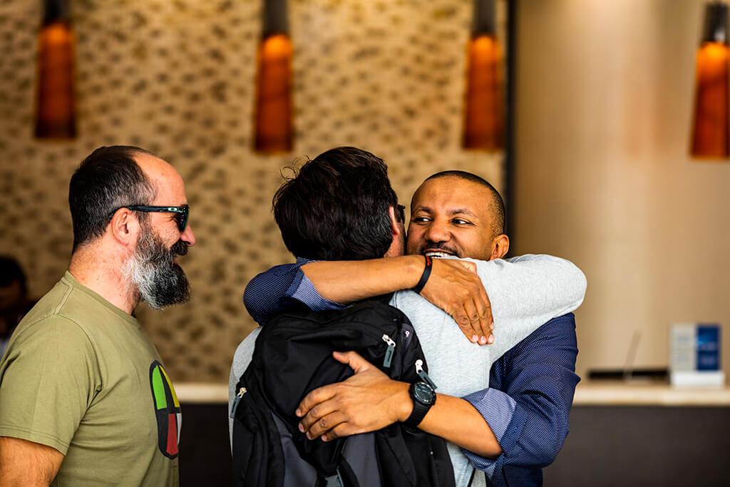 Ethiopian coffee producer, Sam, hugging Coffee Island staff