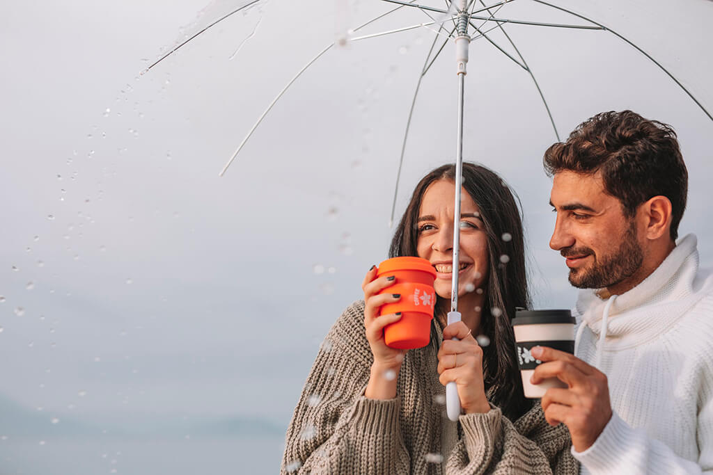 A man and a woman under their umbrella holding their coffee island reusable cups.