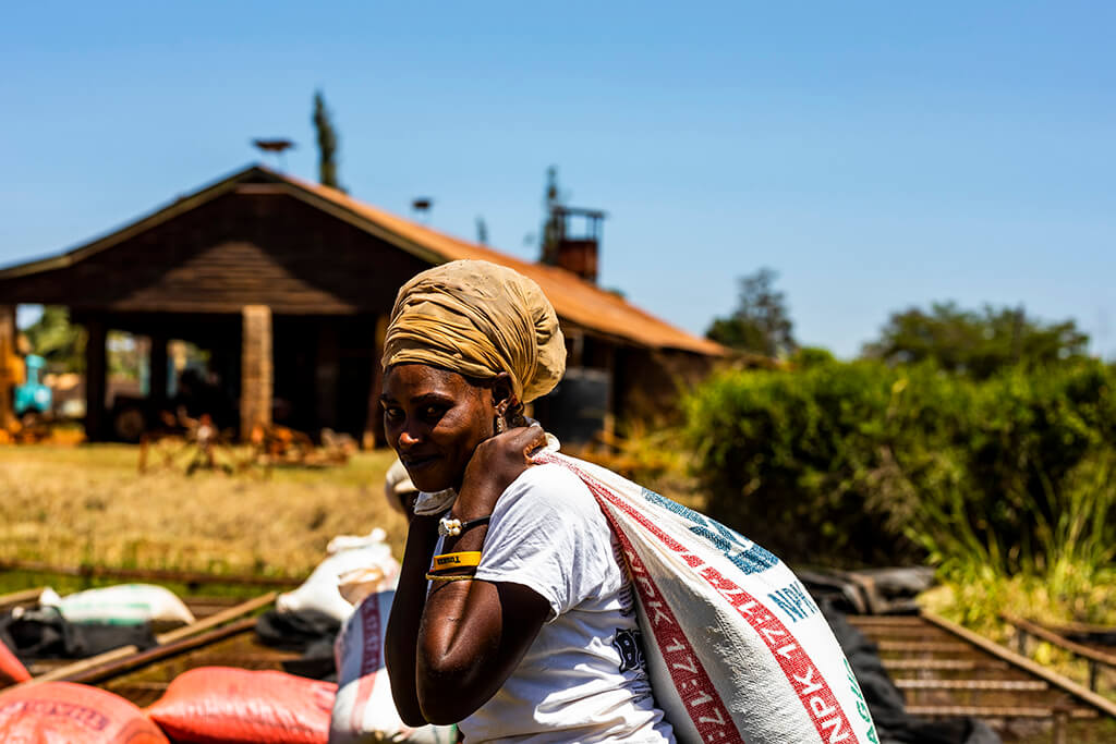 Coffee Island International Women's Day, a woman carrying a sack of coffee beans.