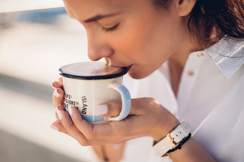 A woman drinking Coffee Island hot chocolate.