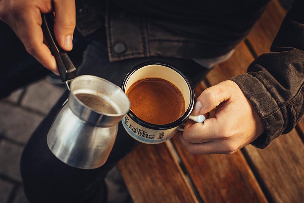 A man pouring ibrik coffee in a mug.