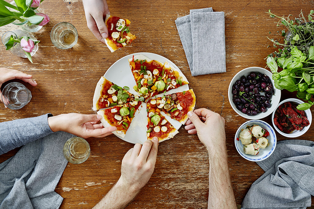 A group of people eating and enjoying a vegan/vegetarian pizza.