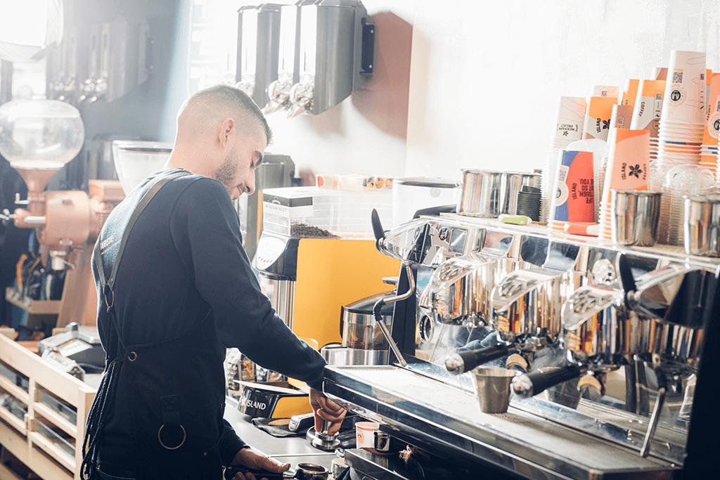 A Coffee Island's barista making coffee.