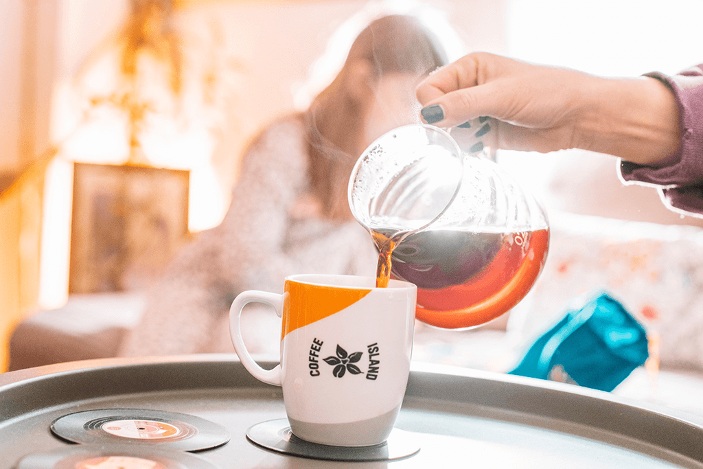 A woman pouring filter coffee in a Coffee Island mug.