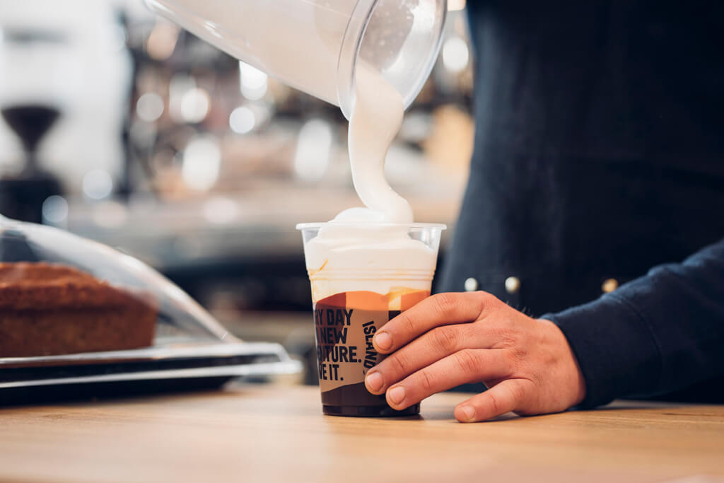 A Coffee Island's baristi preparing a freddo cappuccino.
