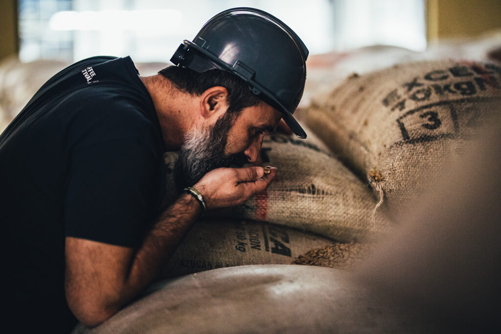 A man smelling coffee beans