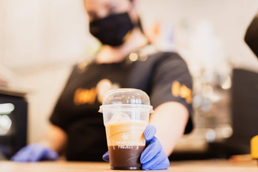 Coffee Island's barista holding an ethiopia adola cup