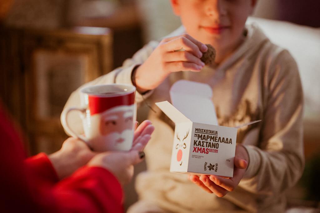 Coffee Island's Santa Claus mug and child eating Coffee Island's cookie bites.