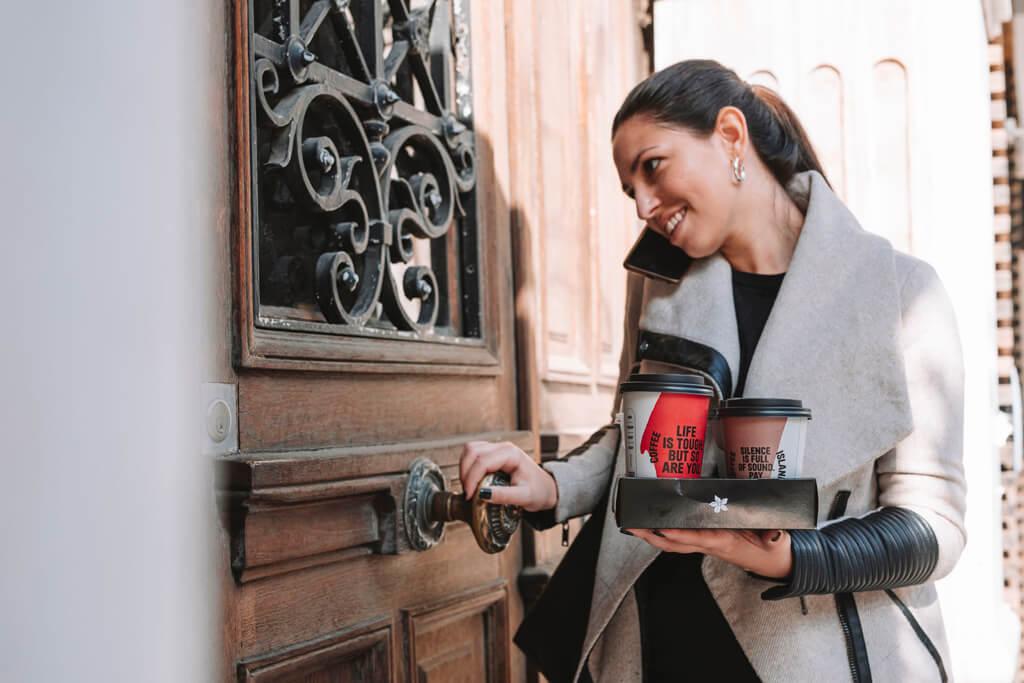 Woman holding two Coffee Island coffees.